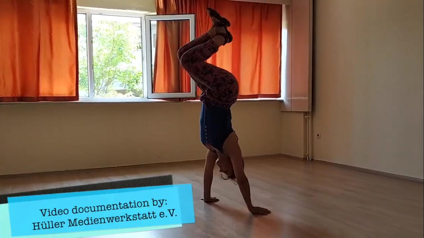 Screenshot aus dem Projekt ''Share the move digital'' von einem Mädchen, die ein Handstand macht.